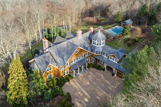The gated main property is set in a heavily wooded area.