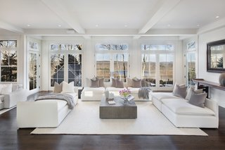 The light-filled living room in the main house has full-height windows showcasing views of the Croton reservoir.