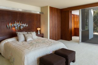 The master suite features wood paneling and extensive glazing, in keeping with the design of the home.