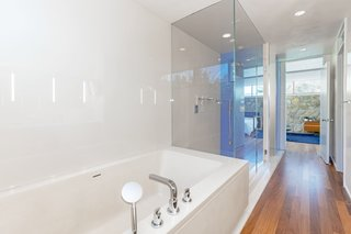 The renovated master bathroom features minimalist, glossy finishes.