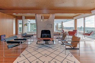 The living room features full-height, wraparound walls of glass and elegant wood details—however, the highlight is a lovely bush-hammered concrete fireplace.