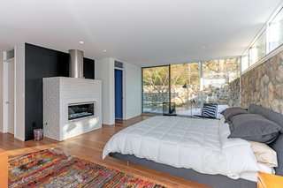 The master bedroom is located in its own wing, and it features a cozy gas fireplace and its own terrace. An inlaid stone wall runs from the exterior terrace into the space, establishing a strong connection with the outdoors.