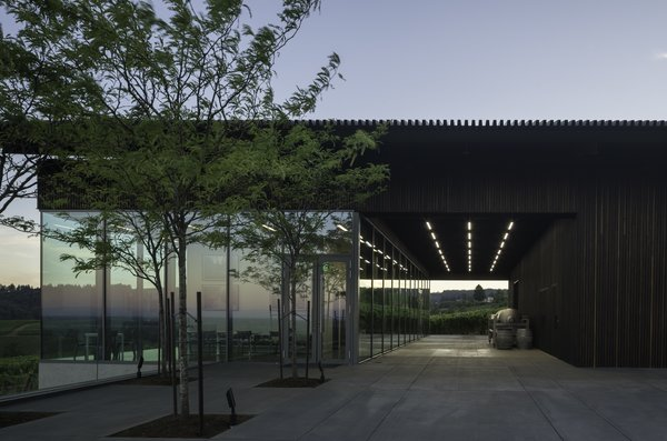 """Waechter Architecture expanded and re-clad the existing winery with a vertical 2"""" x 2"""" blackened cedar screen. During the day, the body of the building takes on a solid appearance. At night, the screen takes on an ethereal, translucent character as interior illumination backlights the vertical cedar ribs."""