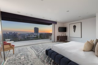 The penthouse-level master suite opens to a balcony with sweeping city views.