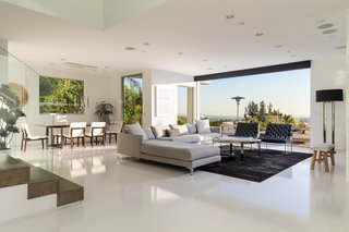 The living room fully opens and extends to the terrace, allowing for indoor/outdoor living.