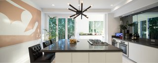 The sleek, modern kitchen is perfect for cooking and entertaining, with a large island and designer appliances.
