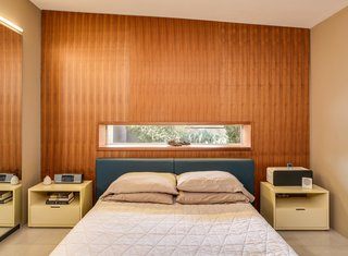 The master bedroom features a textured wall and a long, rectangular window.
