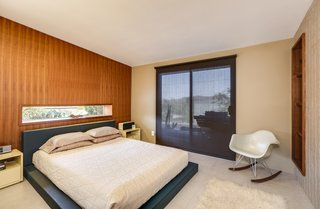 The master bedroom has sliding doors that lead outside.