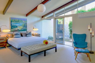 The master bedroomalso enjoys outdoor access, while a vaulted ceiling contributes to a sense of space.