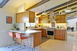 The kitchen updates remain true to the home's midcentury character. Terrazzo tiles are used throughout the home.