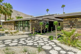 The long, low-slung facade of carefully masoned stone helps integrate the home into its desert surroundings.