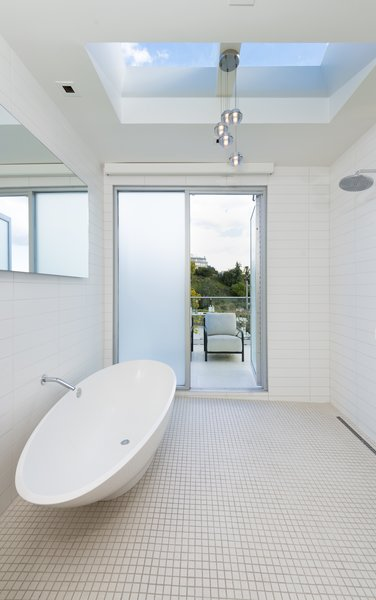The highlight of the master bathroom suite is the oval-shaped soaking tub with a skylight above. A sliding door leads out to a terrace.