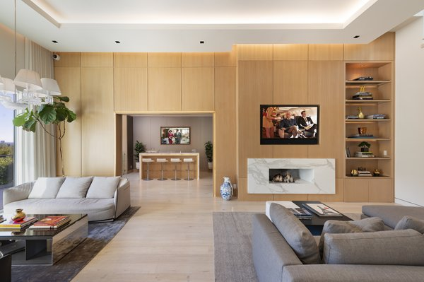 The high-ceilinged living space is designed for comfortable entertaining and features light wood paneling, a marble-framed fireplace, and an elegant bar off to the side.