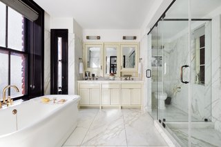 """Roman & Williams designed the bathrooms with """"the look and feel of a grand European hotel"""". The double vanity is painted a high-gloss cream and slabs of Calacatta marble is mixed with brass fixtures makes the master bath shine."""