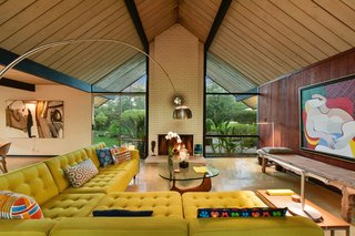 The open-plan living room features classic midcentury elements such as a tall vaulted ceiling, full-height glazing, and a strong brick fireplace.