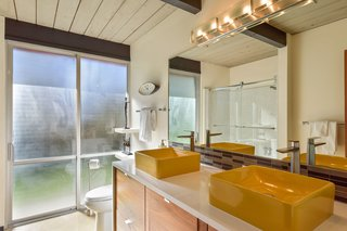 In the guest bath, a glass sliding door leads outside.
