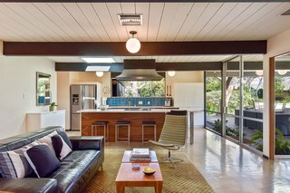 The kitchen overlooks a sitting room, which is perfectly appointed for hosting and indoor/outdoor entertaining.
