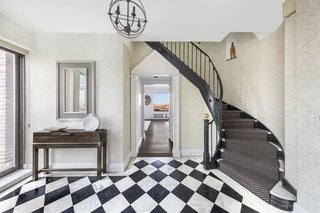 The duplex features a dramatic black-and-white entry with a glamorous circular staircase.