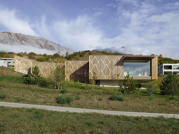 A Green-Roofed Family Home Frames the Grandeur of the Swiss Alps