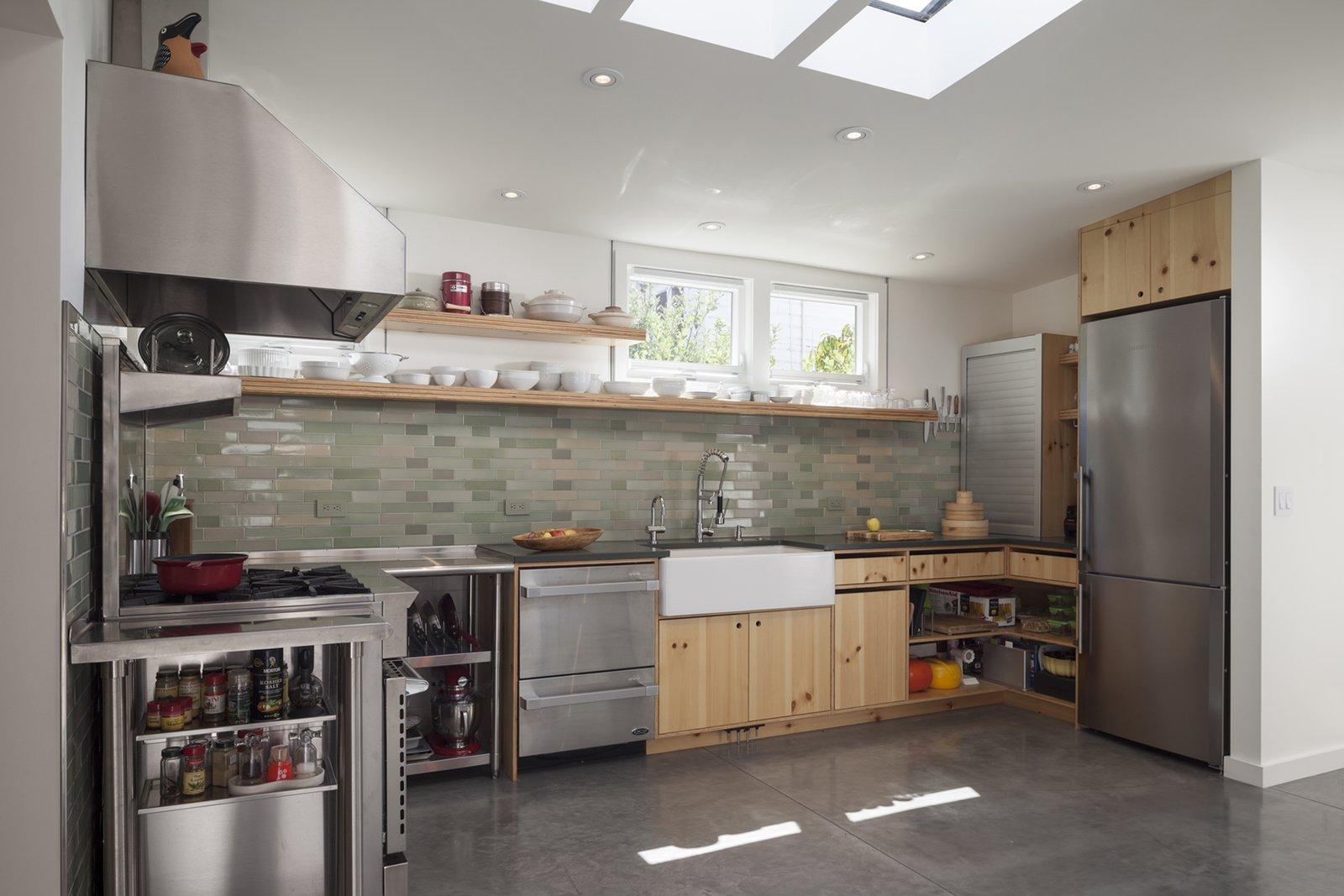 Kitchen, Granite Counter, Metal Counter, Wood Cabinet, Concrete Floor, Glass Tile Backsplashe, Recessed Lighting, Range, Drop In Sink, Refrigerator, and Range Hood  Shotwell Residence by Todd Davis Architecture