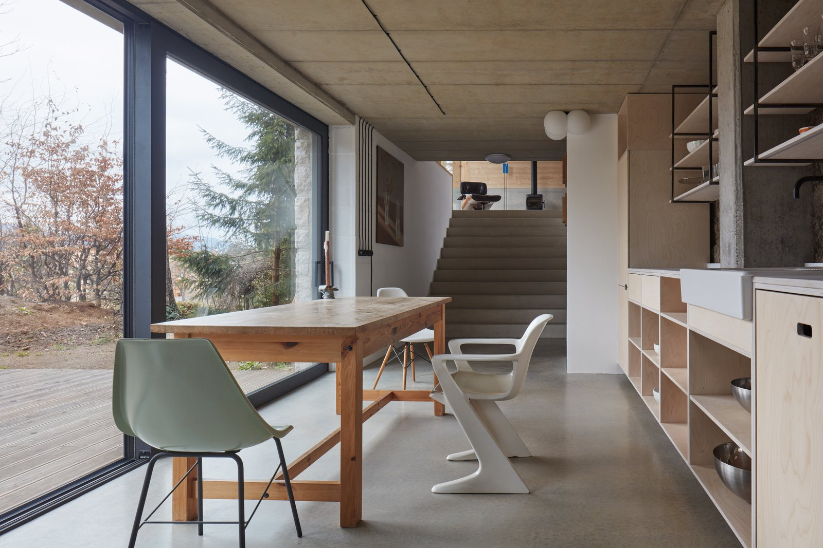 Dining Room, Chair, Ceiling Lighting, Table, and Concrete Floor  House Behind the Wall by BoysPlayNice Photography & Concept