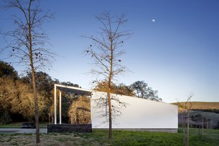 An oversized shed roof covers both the interior of a pool pavilion and an open front porch on a ranch in California.