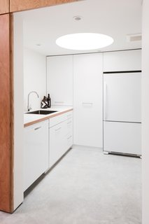 The kitchen has a low ceiling with an inset circular skylight that creates a tubular glow.