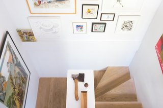 The whitewashed oak staircase, flanked with a salon-style art display.