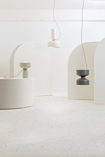Spotlight Volumes — Design, Lukas Peet<br><br>A pendant light with two shades, made from a combination of four possible shade types. Each end has an LED globe bulb to illuminate both above and below. The electrical cord acts as an additional design feature, wrapping around the midsection and gently curving towards the ceiling.