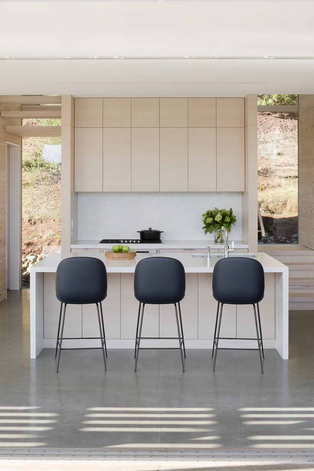 Kitchen, Wood Cabinet, and Concrete Floor  Photo 5 of 11 in A Minimalist House Stands Out in a Wild Landscape from Sunrise