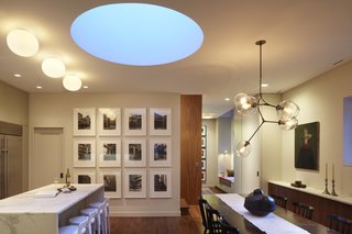 A dining room and kitchen benefit from the pale blue light that comes in through a skylight at dusk.