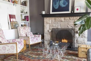 A fireplace anchors the couple's living room, which is adorned with modern artwork as well as beloved curios.