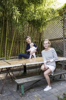 Lara, Ethan, and their baby daughter relax on their back patio, shaded by bamboo.
