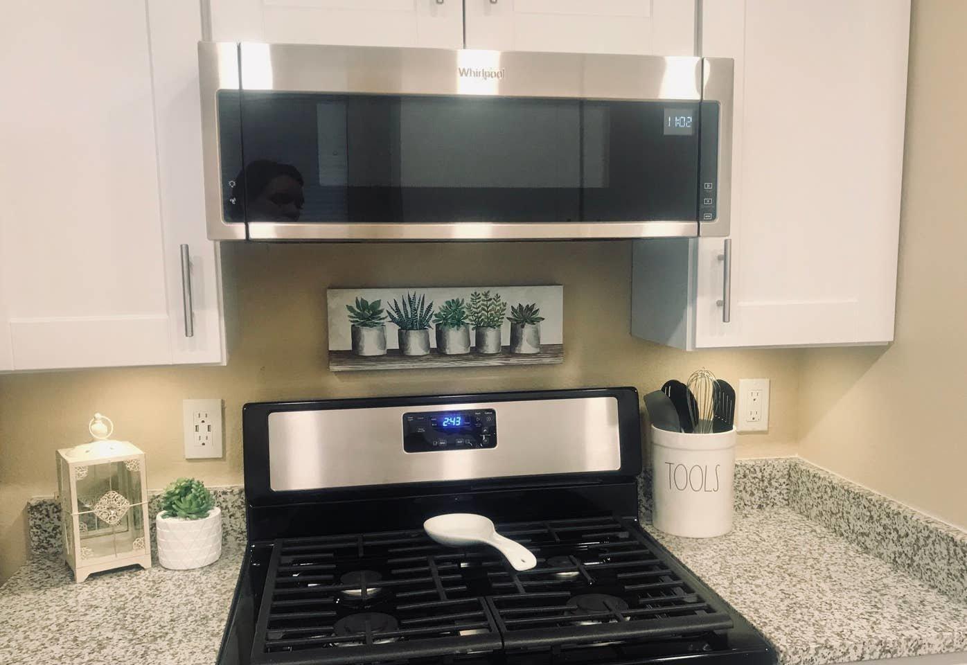 Kitchen, Accent Lighting, White Cabinet, Stone Slab Backsplashe, Range, Vinyl Floor, Granite Counter, Microwave, and Range Hood  Nakomis Dwellings