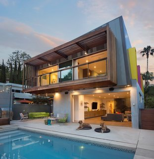 "The ""hanging"" porch and open den areas of this modern Los Angeles home are integrated into the outdoor space, allowing the homeowners to enjoy the California weather. The exterior wood siding is just one of the many stunning architectural elements."