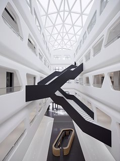 Stark, angular staircases traverse the building's sleek white interior.