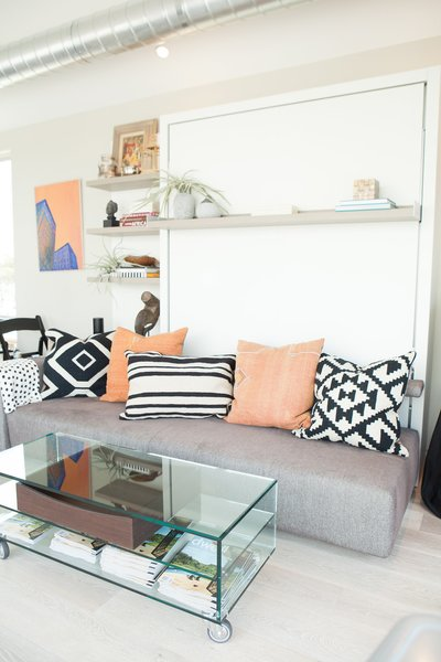 """The transforming wall bed system and accompanying glass coffee table by Resource Furniture modeled a space-saving solution for compact quarters. As the home travels from stop to stop, its furnishings evolve to conversate with the aesthetic of the host city.<span style=""""line-height: 1.8;"""">For San Francisco, Courtney Lake of Monogram Decor used a palette of blue, orange, and gold to evoke a youthful energy and recall the Golden Gate Bridge spanning bay waters.</span>"""