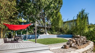 The backyard features a treehouse, wrapped around a robust ficus tree, and a rope swing over a grassy lawn.