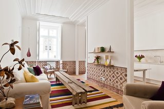 Alorna, a one-bedroom apartment, faces the south and enjoys plenty of light. The 19th-century tiles were removed and carefully cleaned before being reinstalled; they also provided the color inspiration for the Mizette Nielsen rug.