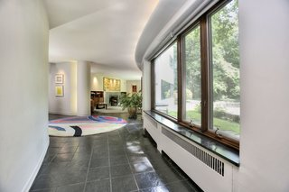 """A Curvaceous Connecticut Home Asks $2.6M - Photo 3 of 8 - A meandering corridor connects the dining room and living room. Labatut notes that """"the absence of parallelism between walls and the absence of doors gives a great fluidity and value to space, yet privacy is insured...by the curving and treatment of walls."""""""