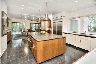 A Curvaceous Connecticut Home Asks $2.6M - Photo 6 of 8 - Bruce Lynn updated the kitchen and installed a new furnace and air conditioning. For furnishings, Lynn initially sought art deco and Biedermeier pieces at furniture auctions. Over the years, works by celebrated designers have become more available, such as Noguchi glass coffee tables and Frank Lloyd Wright chairs. Nearly all the hardware in the house is original; the doorknobs came from the same manufacturer that supplied Philip Johnson's Glass House.