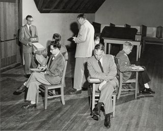 "The IPAR staff conducts a practice run of the Bingo Test, a ""situational procedure involving group interaction."" Wallace Hall, the institute's chief deputy, is seated in front."