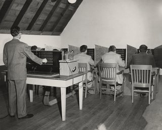 This Book Unearths a Midcentury Personality Study on Architectural Giants - Photo 4 of 13 - Researchers simulate the Conformity Test. In this scenario, five subjects in private booths estimate distances after a light indicates the other participants' answers—the supplied answers are fake, however, allowing this test to measure the effect of peer pressure on judgment. While Victor Lundy saw through the deception, others deferred to the false responses.