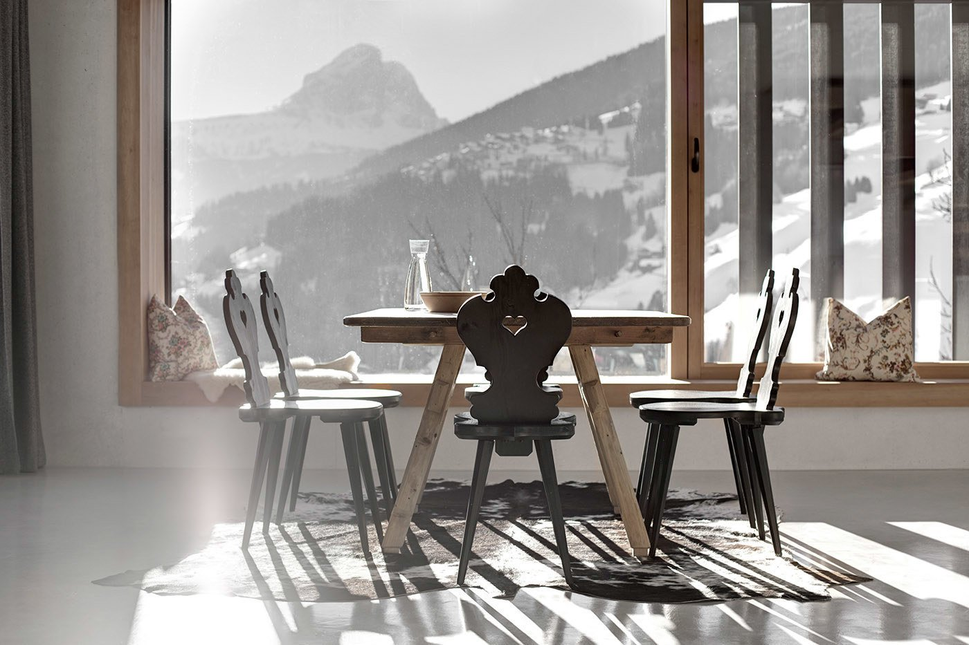 Dining Room, Chair, Table, Bench, Concrete Floor, and Rug Floor The kitchen and dining room enjoy panoramic mountain views. Local pine was hand-hewn for the flooring, windows, doors, and furniture throughout the residence.  Photo 5 of 12 in Find Sanctuary in This Chalet in the Italian Alps