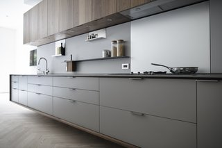 In a Henrybuilt kitchen system, every detail helps orchestrate a streamlined experience. For example, the pulls above protrude to match the plane of the counter and end panels. Drain fields are milled onto work surfaces to fit custom cutting boards and colanders, and low energy LED lights are morticed into the bottom of wall units, which have scoops instead of handles.