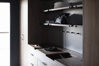 The Wardrobe System features sliding wooden valet trays, leather lined storage compartments, custom interior felt door pockets, handcrafted leather pulls, and an integrated laundry hamper.