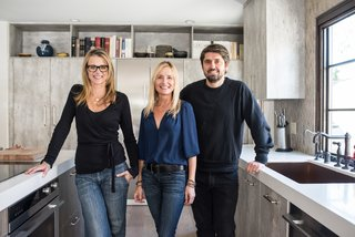 "Krissy Lefebvre, left, and Ludo Lefebvre, right, pose in the redone kitchen with their designer Ginny Capo, who is based in Santa Monica. ""Ginny did a great job of marrying modern appliances with old world materials to give us a perfectly balanced, updated, and truly functional space,"" says Lefebvre.​"