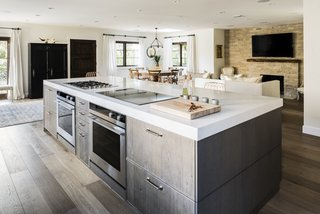 The gas and induction cooktop, along with the two ovens below, face the bar seating at the kitchen island, allowing Lefebvre to interact with his guests while preparing meals.