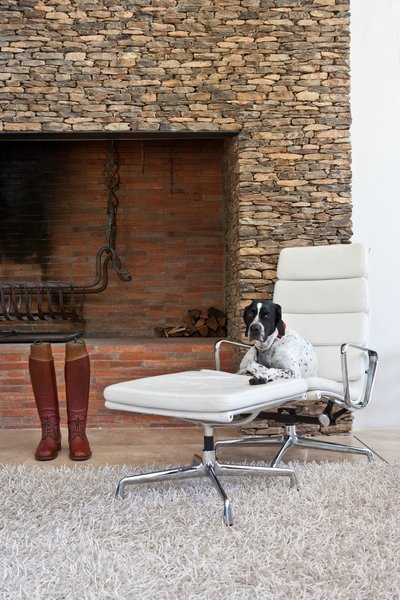 Living Room, Wood Burning Fireplace, Rug Floor, Standard Layout Fireplace, Ottomans, and Recliner In the living area, a dry packet stone fireplace frames a fire grate that was forged by an expert blacksmith.  Photo 17 of 25 in Leap Into the Year of the Dog With These 25 Pups in the Modern World from This South African Villa Lets You Bask in Divine Views