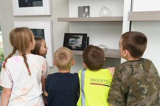 Young visitors watched a video about Resource Furniture, whose Murphy bed was a space-saving solution in the home.